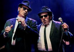Two men in suits on stage